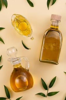 Varietà di bottiglie e bicchiere riempito con olio d'oliva