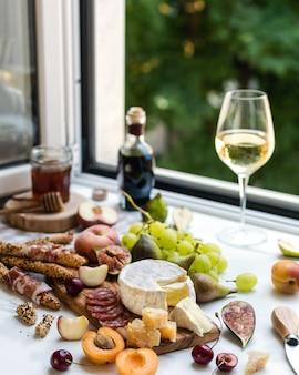 Varietà di camembert, parmigiano, prosciutto e frutta con bicchiere di vino bianco