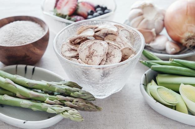 Varietà di cibi prebiotici, banana verde cruda, asparagi, cipolle, aglio, porri, bacche e fagiolini per la salute dell'intestino