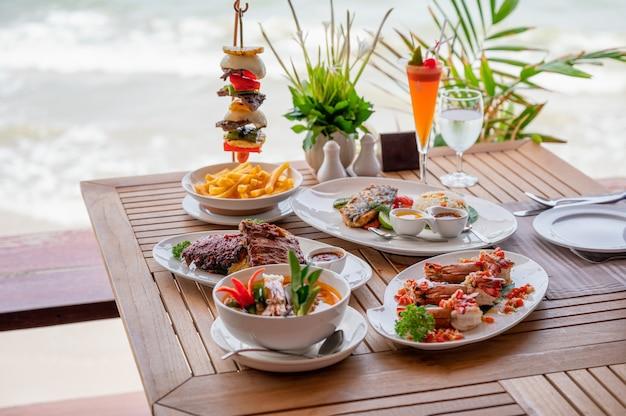 Varietà di cibo, costolette di maiale arrosto, bistecca di manzo, frutti di mare e zuppa piccante sul tavolo da pranzo