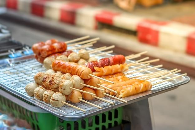 Varietà di cibo di strada stile tailandese di salsiccia fritta nel grasso bollente.