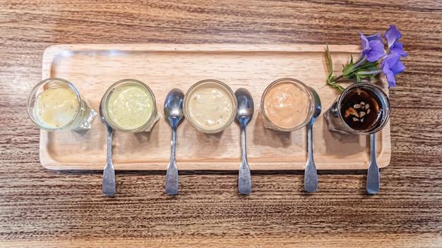 Varietà di condimento per l'insalata sulla tavola di legno