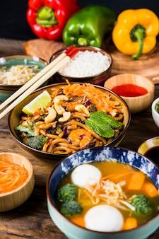 Varietà di delizioso cibo tailandese con le bacchette sul tavolo di legno