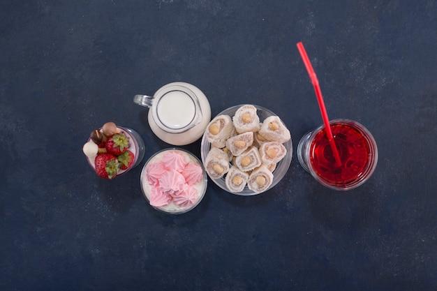 Varietà di dessert con un bicchiere di vino rosso, vista dall'alto.