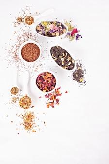 Varietà di diversi tipi di tè. tè alle erbe, nero, verde, rosso, alla frutta. bevande disintossicanti, calmanti, antiossidanti, tonificanti e rinfrescanti