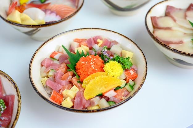 Varietà di donburi tagliata a dadini di pesce crudo con verdure su riso giapponese