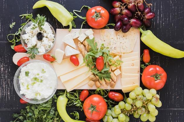 Varietà di fette di formaggio e cubetti con uva, pomodori; peperoncini verdi; foglie di rucola e prezzemolo su sfondo nero