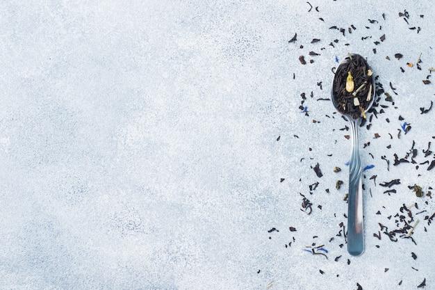 Varietà di foglie di tè e fiori secchi in cucchiai su sfondo grigio copiare lo spazio