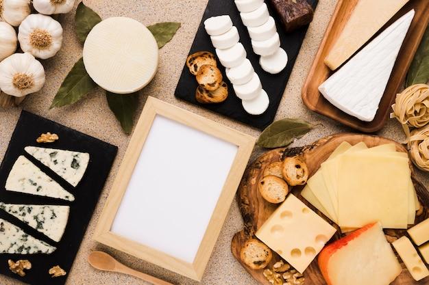 Varietà di formaggi e ingredienti sani con cornice bianca vuota su sfondo texture