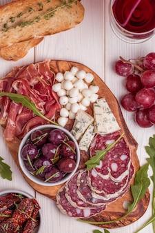 Varietà di formaggio e carne, olive, uva, rucola sul tavolo bianco