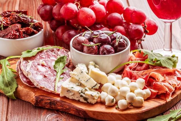 Varietà di formaggio e carne sul tavolo scuro.