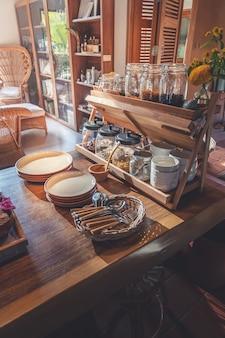 Varietà di grano e semi di piante con piante di insalata e condimento di alimenti sani in ciotola di legno sul tavolo di legno