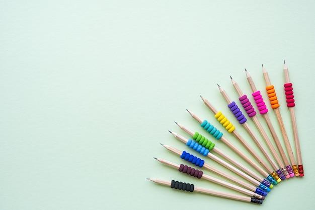 Varietà di matite eco con impugnatura colorata su sfondo verde, copia spazio, vista dall'alto
