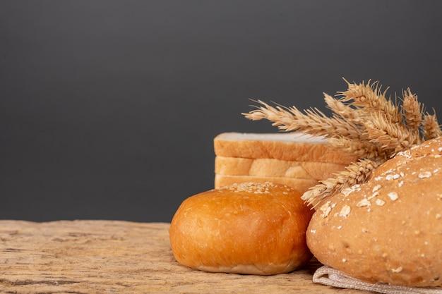 Varietà di pane sulla tavola di legno su un vecchio fondo di legno.