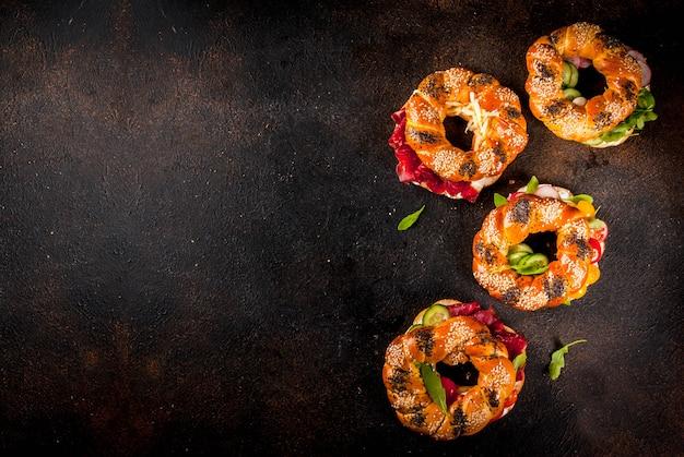 Varietà di panini bagel fatti in casa con semi di sesamo e papavero, crema di formaggio, prosciutto, ravanello, rucola, pomodorini, cetrioli, sfondo scuro cemento copia spazio sopra