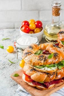 Varietà di panini bagel fatti in casa con semi di sesamo e papavero, crema di formaggio, prosciutto, ravanello, rucola, pomodorini, cetrioli, superficie strutturata grigia bianca