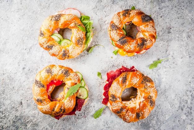 Varietà di panini bagel fatti in casa con semi di sesamo e papavero, crema di formaggio, prosciutto, ravanello, rucola, pomodorini, cetrioli, vista superiore superficie bianca grigia