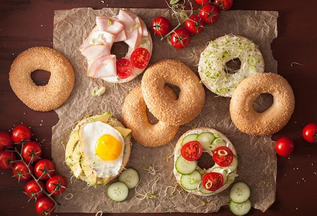 Varietà di panini su ciambelle: uovo, avocado, prosciutto, pomodoro, formaggio a pasta molle, germogli di erba medica