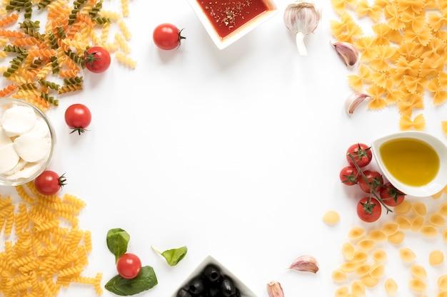 Varietà di pasta cruda con ingrediente sulla superficie bianca