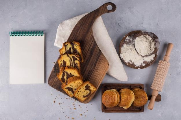 Varietà di pasticcini e cracker su una tavola di legno con un libro di cucina a parte