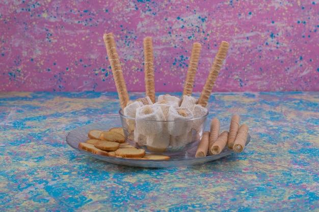 Varietà di pasticcini in tazza di vetro e piatto su sfondo blu