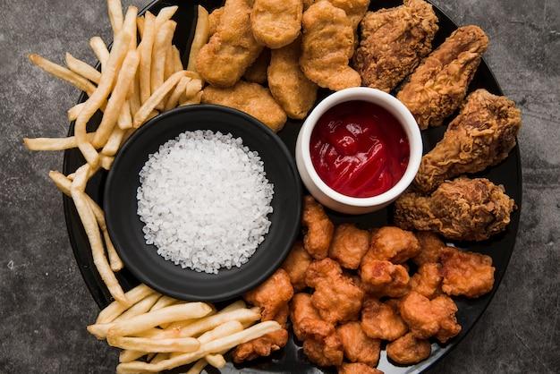 Varietà di piatti a base di pollo; patatine fritte con sale e salsa di pomodoro in lamiera
