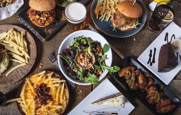 Varietà di piatti, hamburger classici fatti in casa insalata di formaggio di capra, patatine fritte e dessert sul tavolo di legno. menu del menu del ristorante.