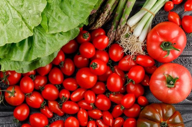 Varietà di pomodori con lattuga, asparagi, cipolle verdi sulla parete di legno, piatto disteso.