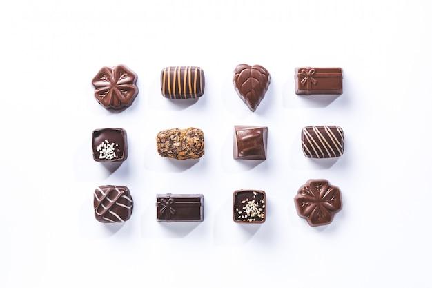 Varietà di praline di cioccolato, simmetriche isolate su bianco. dolce e cioccolato.