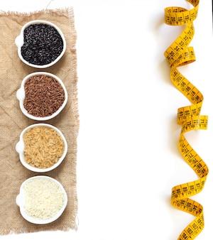 Varietà di riso in ciotole isolate sulla vista superiore bianca con lo spazio della copia
