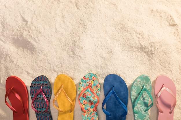 Varietà di sandali infradito colorati sulla sabbia