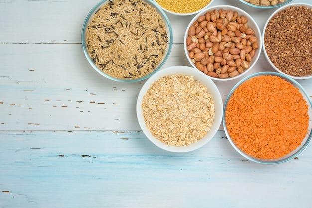 Varietà di semi biologici naturali in piatti rotondi di lenticchie, ceci e riso integrale lungo, grano saraceno, miglio.