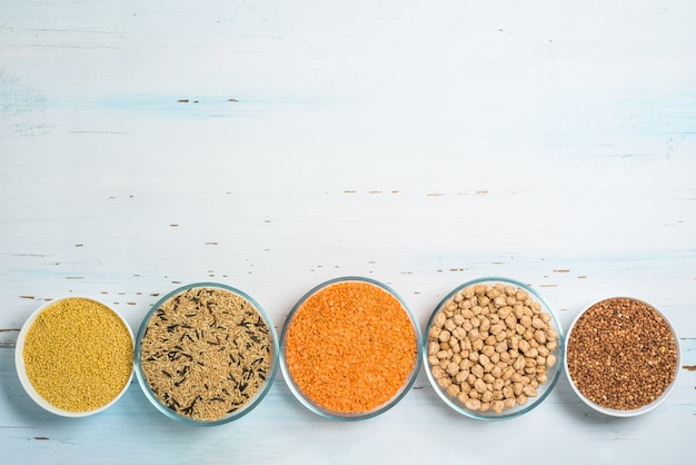 Varietà di semi biologici naturali in piatti rotondi di riso, miglio, lenticchie, grano saraceno, arachidi, farina d'avena. la vista dall'alto.
