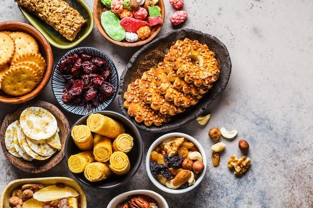 Varietà di snack e dolci su sfondo grigio. cialde, noci, dolci, biscotti, patatine e frutta, vista dall'alto.