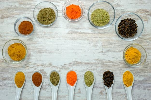 Varietà di spezie esposte in cucchiai e ciotole