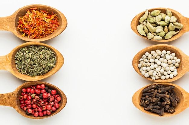 Varietà di spezie in cucchiai di legno allineati