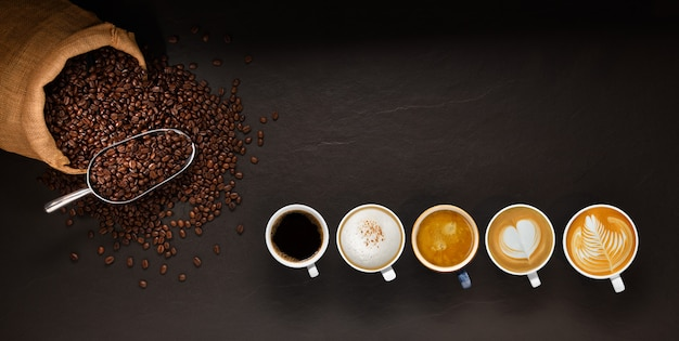 Varietà di tazze di caffè e chicchi di caffè nel sacco di iuta su sfondo nero