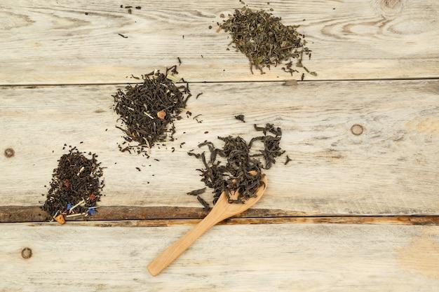 Varietà differenti di tè naturale su un cucchiaio di bambù su un fondo di legno