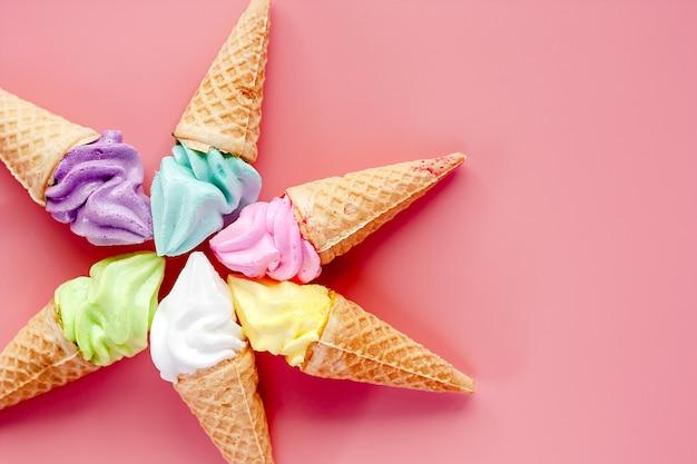 Vario del cono gelato su sfondo rosa per dolce e rinfrescante concetto di dessert