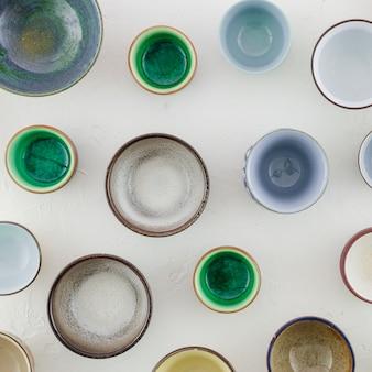 Vario tipo di tazze di tè ceramiche isolate su fondo strutturato bianco
