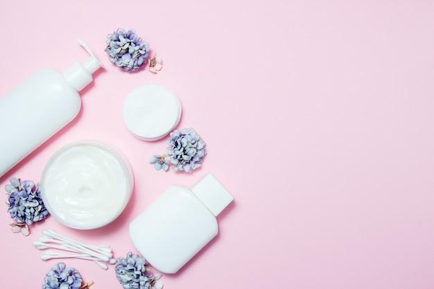 Vasetti bianchi di cosmetici con fiori rosa