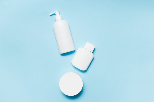 Vasetti bianchi di cosmetici su sfondo blu