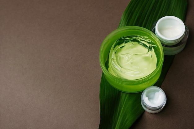 Vasetti di crema bianca idratante e gel di aloe verde su una foglia di palma.