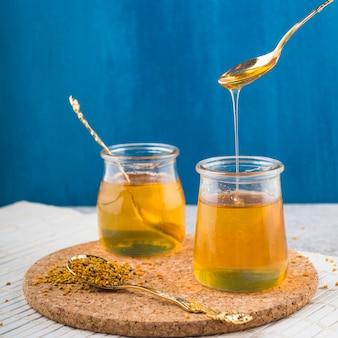 Vasetti di miele e cucchiaio con polline d'api su sottobicchiere di sughero