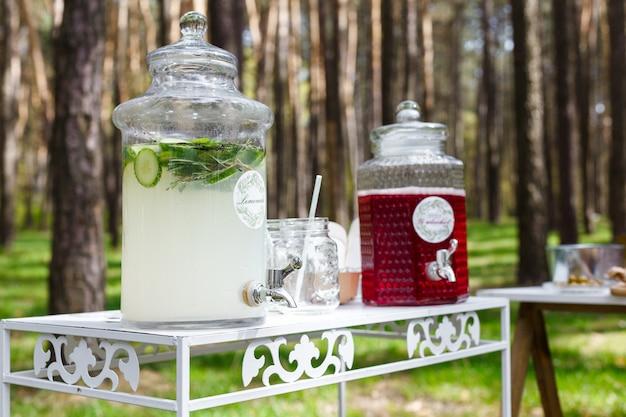 Vasetti di vetro con limonata fresca e snack su tavoli di legno