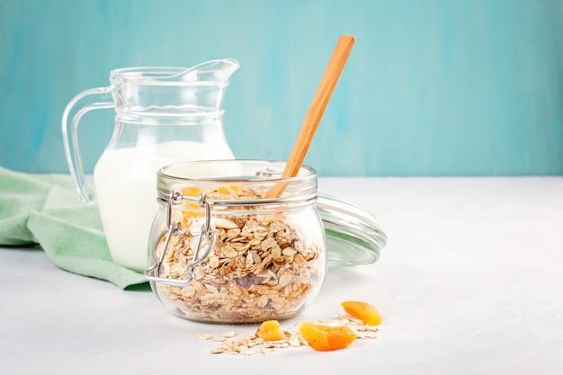 Vasetto con muesli fatto in casa con muesli o farina d'avena con noci e frutta secca e latte.
