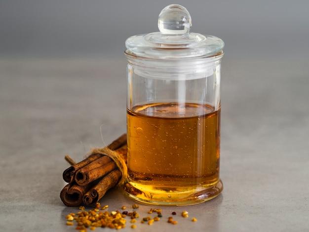 Vasetto di miele accanto a bastoncini di cannella