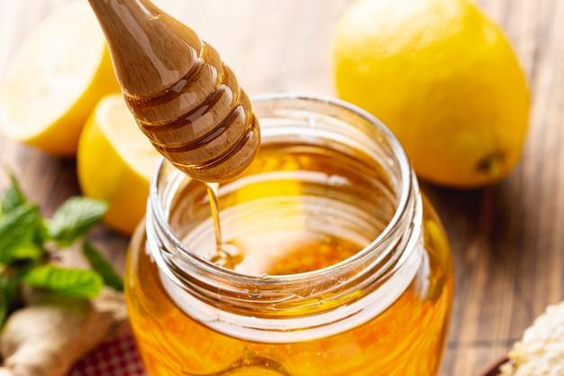 Vasetto di miele con mestolo di legno
