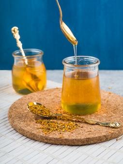 Vasetto di miele con polline d'api sul cucchiaio sopra le montagne del sughero