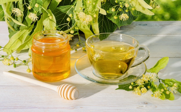 Vasetto di miele di tiglio, cappuccio di tè di tiglio e ramo con fiori di tiglio in una giornata di sole